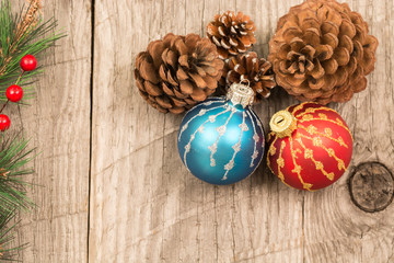 Red and blue Christmas baubles and pine cones