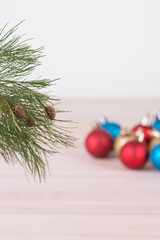 Pine tree branch with colorful Christmas baubles background