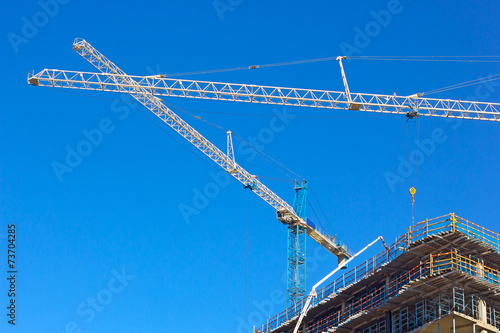 poster of Construction cranes work in synchrony at building site.