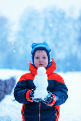 Half-length portrait of boy who stands in winter park holding sm