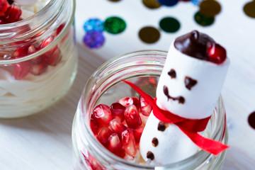 Chrismas dessert with pomegranate  and marshmallow snowman