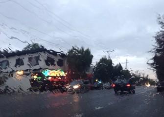 lights blur through wet windshield