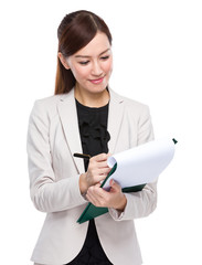 Businesswoman write on clipboard