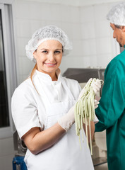 Happy Female Chef Holding Spaghetti Pasta At Kitchen