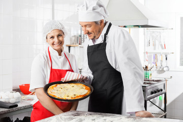 Happy Chef Standing By Colleague Holding Pizza Pan