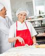 Leinwandbild Motiv Confident Chef Cutting Ravioli Pasta With Colleague In Backgroun