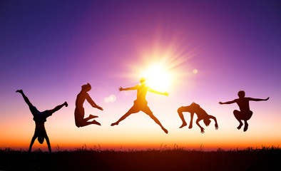 happy young people jumping on the hill with sunlight background