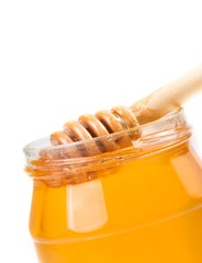 honey jar on white background with wooden honey dipper inside