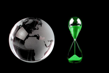 Crystal globe and green hourglass. Conceptual image.