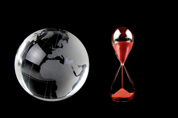 Crystal globe and red hourglass. Conceptual image.
