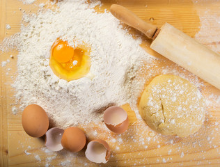 Baking preparation: eggs, flour, rolling pin on a board