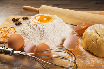 Baking preparation: eggs, flour, rolling pin, spices on a board