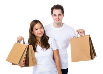 Asian woman and caucasian man holding shopping bag together