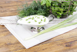 Metal bowl of cream with a tuft of onion, dill and parsley in a
