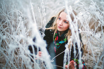 winter girl in the grass covered with frost