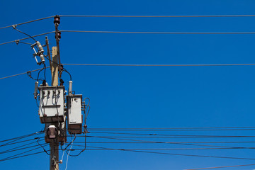 electrical post with power line cables on blue sky