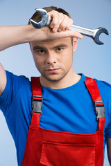 Tired young mechanic in red overall on blue background.