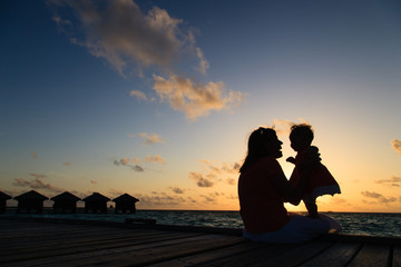 mother and little daughter having fun at sunset