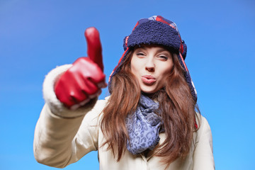 Happy smiling woman with ok hand sign on winter time