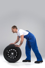 side view of man rolling tire on grey background.
