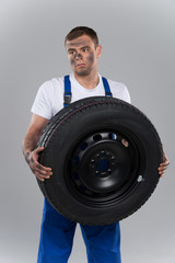 pensive man holding tire on grey background.
