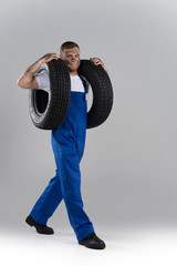happy man carrying tire on grey background.