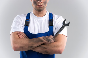 dity young mechanic in blue overall on blue background.