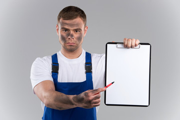 dirty man holding clipboard and showing blank.