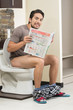 young relaxed man sitting on the toilet reading newspaper - 73713487