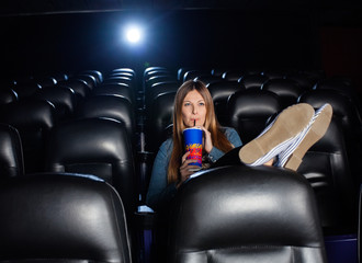 Relaxed Woman Drinking Cola While Watching Movie At Theater