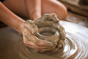 """Potter hands making in clay on pottery wheel"
