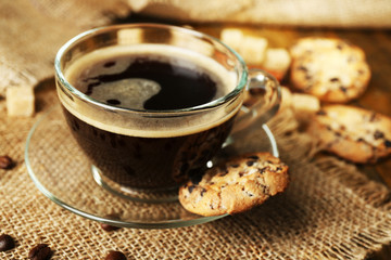 Glass cup of coffee and tasty cookie on wooden background