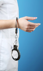 Female hand is handcuffed at  wrist on blue background