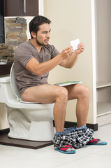worried man sitting on the toilet running out of paper