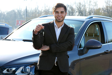 Businessman holding car key outdoors