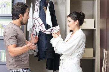 married young couple choosing clothes in the closet