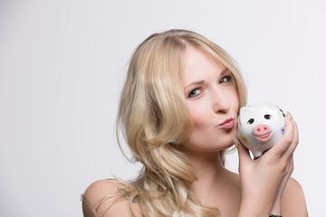 Hübsches Mädchen küsst Sparschwein