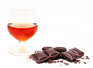 Glass with cognac and chocolate bars stack isolated on a white