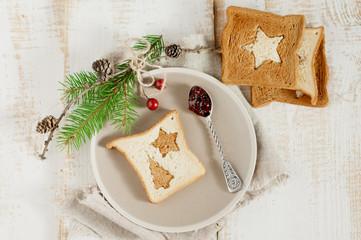 Chrismas breakfast. Spoon berry jam and slice toast bread on woo