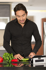 handsome young modern man cooking healthy recipe and using