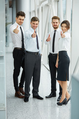 Successful young business people showing thumbs