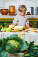 Little chef boy is cooking vegetables in the rural kitchen