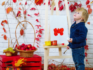 Little boy in autumn location painting red apples