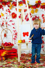 Cute little boy painting apples in autumn