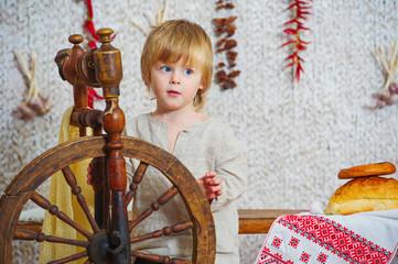 Little boy near vintage spinning wheel in village house