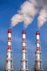Three striped industrial pipes with smoke over cloudless sky