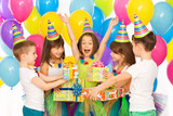 Joyful little kid girl receiving gifts at birthday party - 73720289