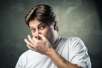 Man with disgusted expression closing his nostrils