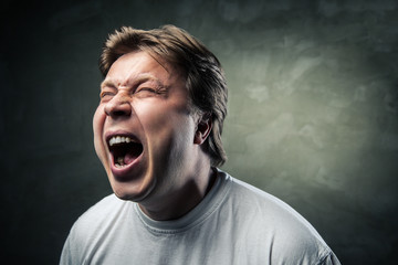 young angry man over dark grey background