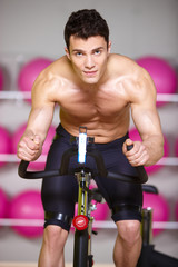 Topless Muscular Man Spinning Gym Bike